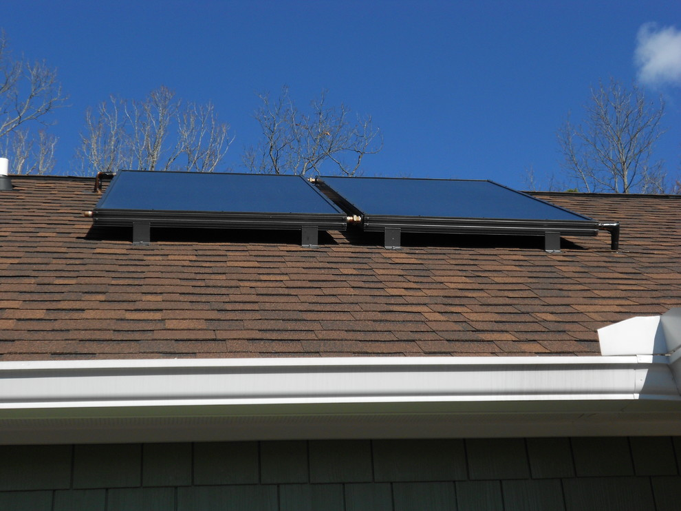 Tankless vs Tank Water Heater for Traditional Exterior with Solar Collectors